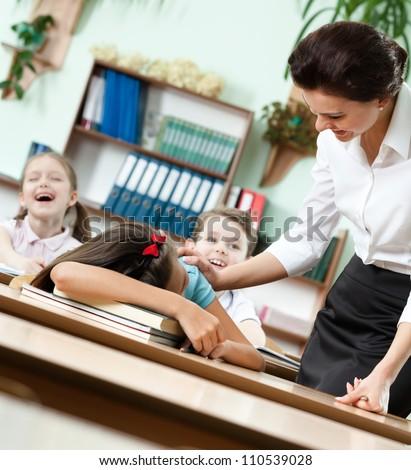 Teacher wakes a sleeping at the desk schoolgirl up - stock photo
