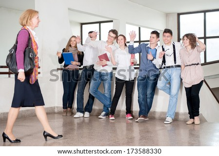 Teacher walking by a group of students in school hall - stock photo