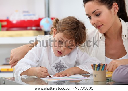 Teacher watching her pupil coloring a drawing - stock photo