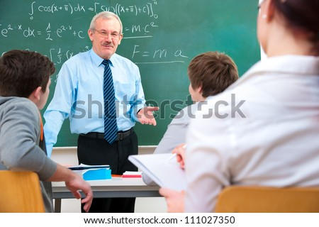 Teacher with a group of high school students in classroom - stock photo