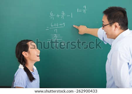 teacher with a little girl discussing  in classroom