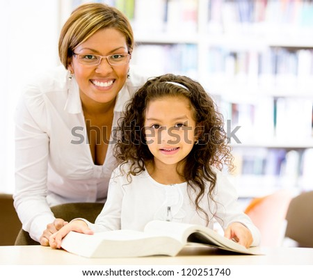Teacher with a young student at the elementary school - stock photo
