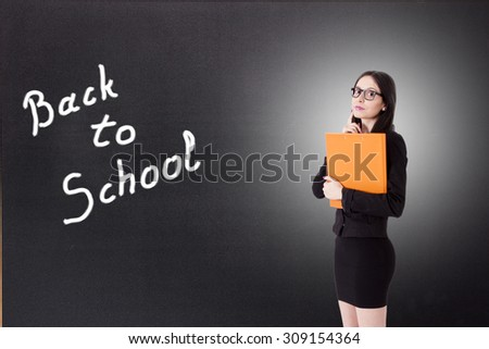 teacher with books on the blackboard