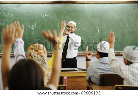 Teacher with children in classroom, boys and girls in school together learning, competition - stock photo