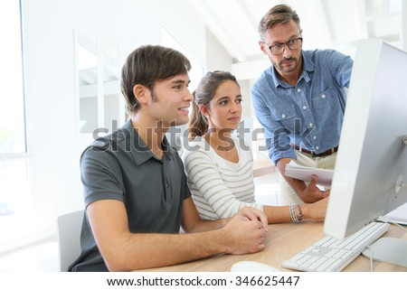 Teacher with group of students in class working on desktop