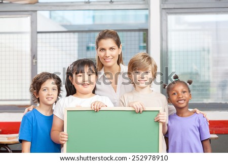 Teacher with happy primary school pupils holding blank chalkboard. - stock photo