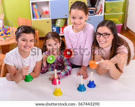Teacher With Kids holding Music Hand Bells in Music School - stock photo