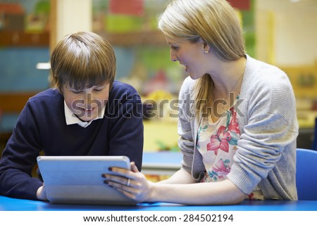 Teacher With Male Pupil Using Digital Tablet In Classroom - stock photo