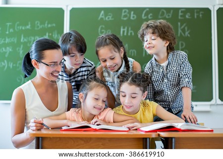 Teacher with pupils in classroom - stock photo