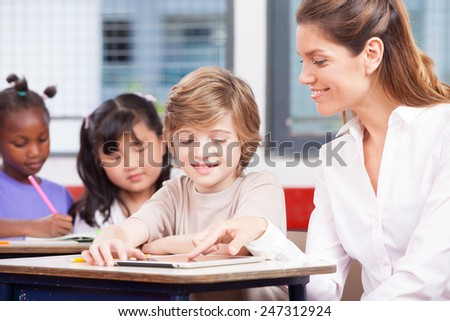 Teacher with schoolboy in a multi ethnic elementary classroom. - stock photo
