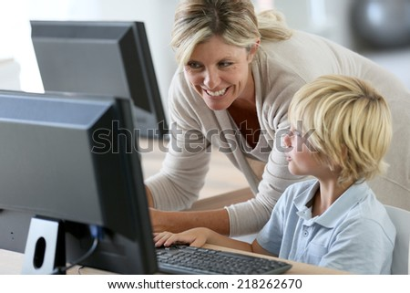 Teacher with schoolboy studying on computer - stock photo