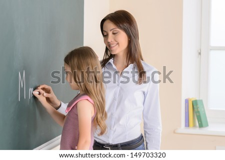Teacher with schoolgirl. Little girl writing letters on the blackboard while teacher standing near her and smiling - stock photo