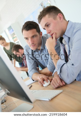 Teacher with student working on desktop - stock photo