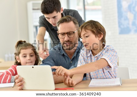 Teacher with students in class using digital tablet - stock photo