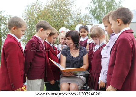 Teacher with students reading a book - stock photo