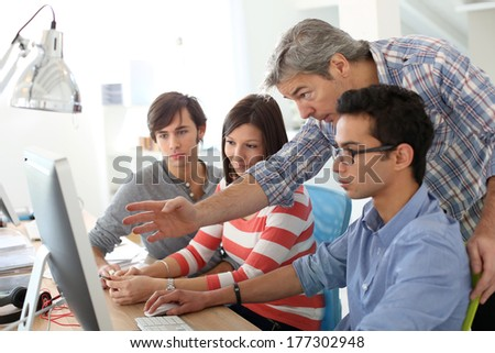 Teacher with students working on desktop  - stock photo
