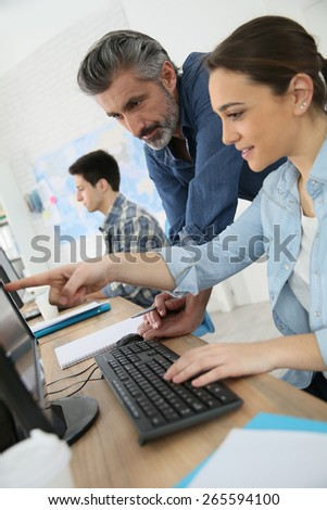Teacher with young people in computing class - stock photo