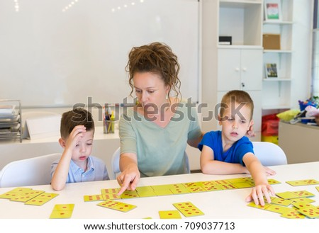 teacher woman play with two child boy domino in classroom