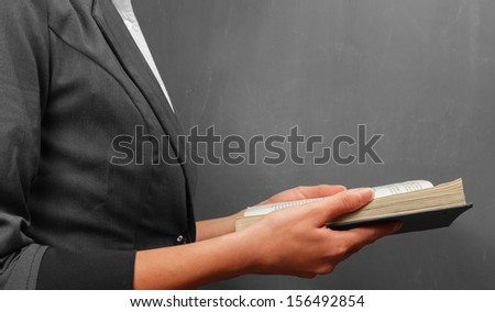 Teacher woman reading a book near a blackboard, side view