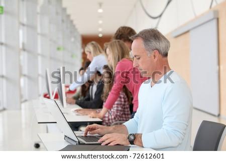teacher working on laptop computer in classroom - stock photo