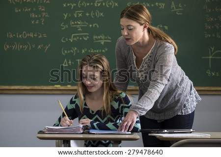 Teacher working with a teen girl in a classroom - stock photo