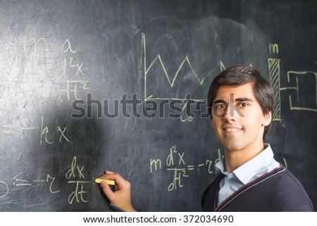 Teacher writing formulas on the blackboard - stock photo