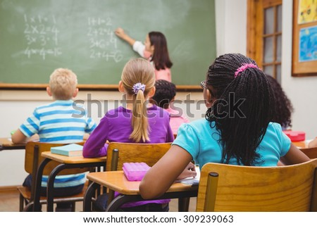Teacher writing on the blackboard at the elementary school