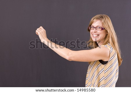 Teacher writing on the blackboard while smiling at students. - stock photo