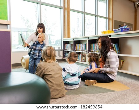 Teachers and elementary students in school library - stock photo