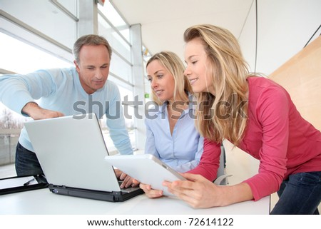 Teachers and teenage girl in front of computer - stock photo