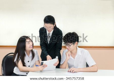 Teachers guide something to Couple asian student in uniform at classroom - stock photo