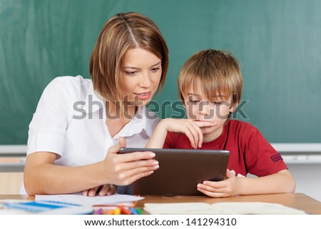 Teaching a boy with a tablet in classroom - stock photo