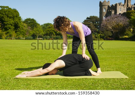 Teaching Yoga in a park - stock photo