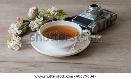 Teacup with retro camera on wooden table