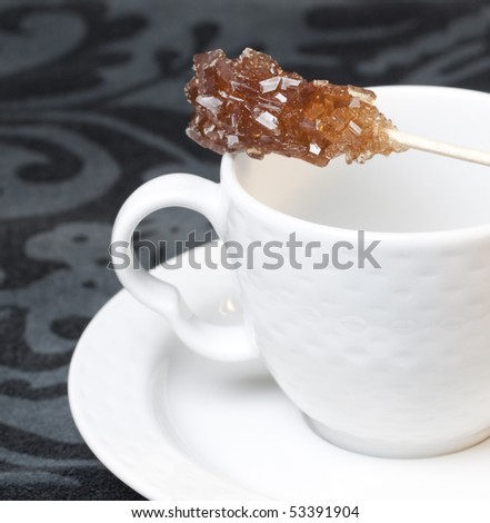 Teacup with sugar stick - stock photo