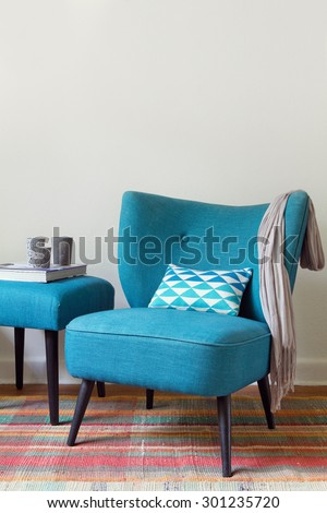 Teal retro armchair and colorful pink pattern rug interior with ottoman - stock photo
