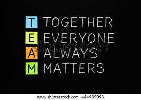 TEAM acronym Together Everyone Always Matters handwritten with white chalk on blackboard. Teamwork concept.