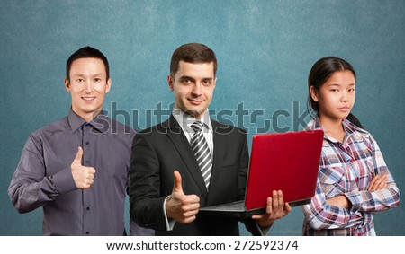 Team and male businessman in suit with laptop in his hands, looking on camera - stock photo