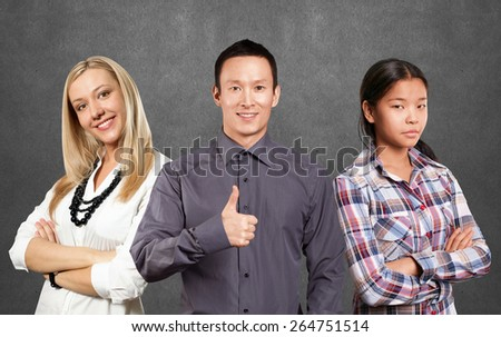 Team and young woman with crossed hands standing against different backgrounds - stock photo