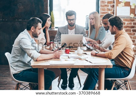 Team at work. Group of six young people reading and looking through charts while sitting at the table in office - stock photo