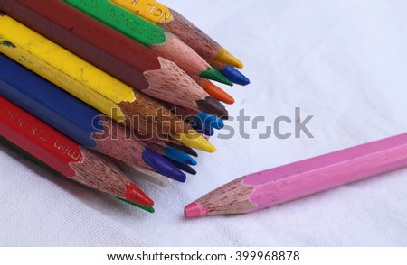 Team brainstorming, high angle view colour pencils Colour Pencils with different one on white background, Business concept - stock photo