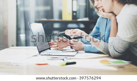 Team brainstorming. Photo young creative managers crew working with new startup project in modern office. Contemporary notebook on wood table. Statistics plans laptop screen. Horizontal, film effect - stock photo