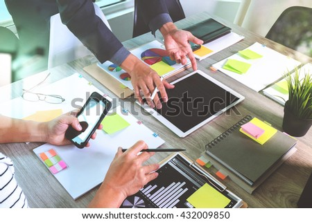 Team business meeting presentation. Hand businessman working new start up project in modern office.Laptop computer and digital table and smart phone on wood table. Horizontal, Sun flare effect photo  - stock photo