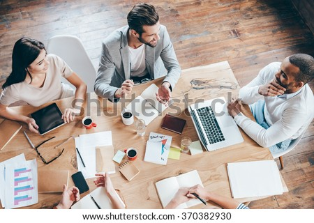 Team communication. Top view part of group of five people discussing something with smile while sitting at the office table - stock photo