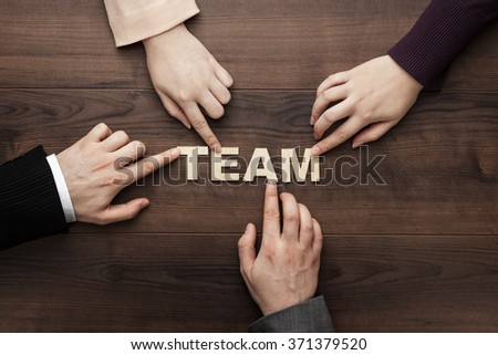 Team concept. Different hands of men and women connect letters into one word on the brown wooden table background. Each has its own role in team - stock photo