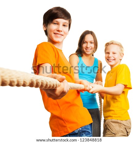 Team concept three happy kids pull the rope - stock photo