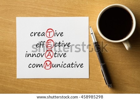 TEAM creative effective, innovative, communicative - handwriting on notebook with cup of coffee and pen, acronym business concept