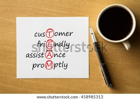 TEAM - Customer, Friendly, Assistance, Promptly- handwriting on notebook with cup of coffee and pen, acronym business concept