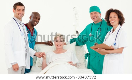 Team Doctors looking at a patients dedside - stock photo