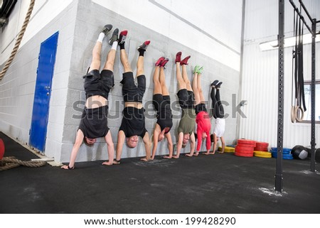 Team exercising handstands at fitness gym center - stock photo